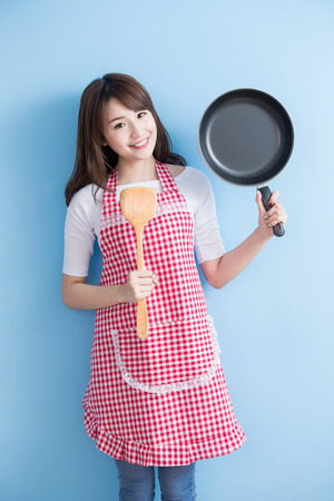 house wife: beauty housewife take wok and rice spoon isolated on blue background