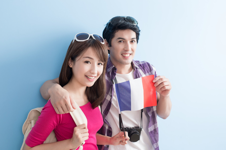 young couple go to travel and take french flag