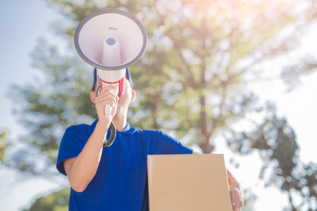 deliveryman hold box and take megaphone, asian Stock Photo