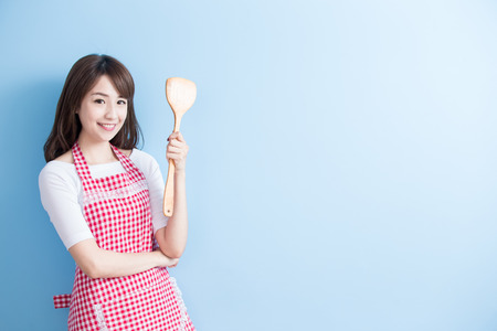 beauty housewife take rice spoon and smile isolated on blue background Фото со стока