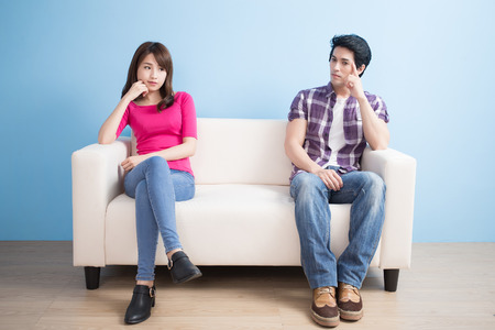 young couple feel bad and look somewhere sit on sofa at home 版權商用圖片