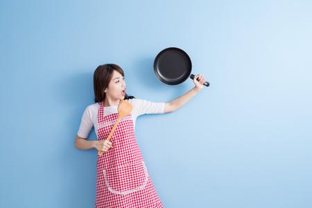 cocineros: la belleza del ama de casa toma wok y arroz cuchara aislados sobre fondo azul Foto de archivo