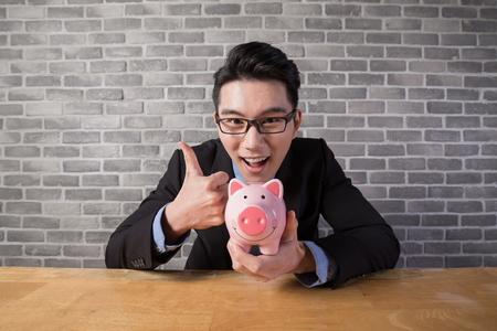 business man take piggy bank in the office, asian 免版税图像