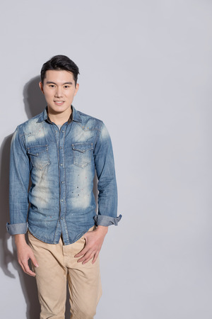 grey: man stand and smile with gray wall, asian