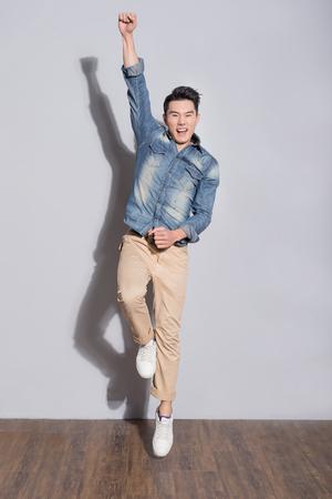 男スタンドと灰色の壁、アジアで笑顔 写真素材