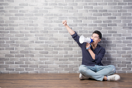 man take microphone and show something with brick wall, asian