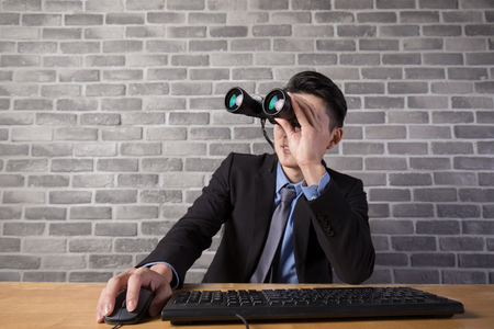 internet search: business man use binocular with brick wall in office,asian