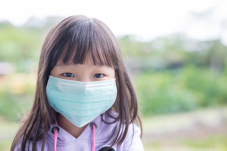 resting: cute little girl get cold wear mask,  asian Stock Photo