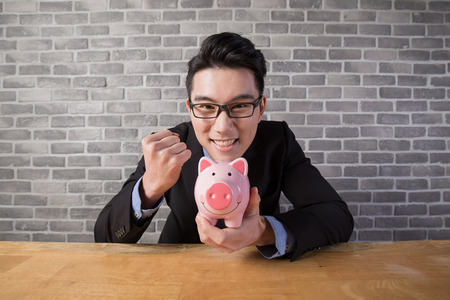 business man take piggy bank in the office, asian Stock Photo
