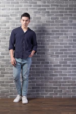 レンガの壁、アジアでハンサムな男スタンド