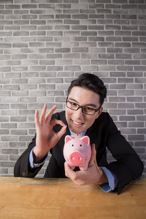 security: business man take piggy bank in the office, asian Stock Photo
