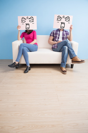 couple on couch: couple hold billboard and sit on sofa at home