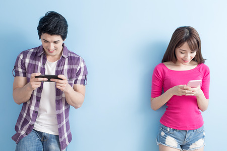 men and women: young couple use phone happily with blue background