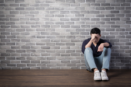 man sit and feel depressed with brick wall ,asian Stock Photo