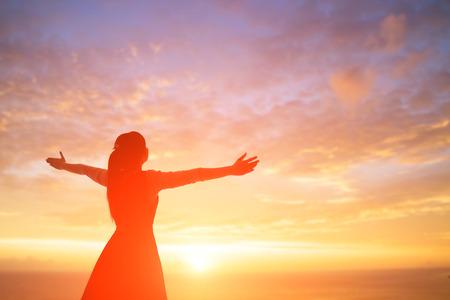 若い女性、日の出に祈る敬虔なアジア