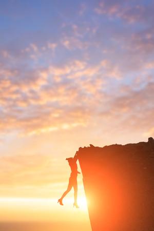 iluminado a contraluz: silhouette of businesswoman with dangerous problem in cliffs