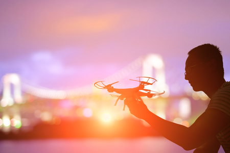 silhouette of man play drone in the sunset with odaiba Stock Photo
