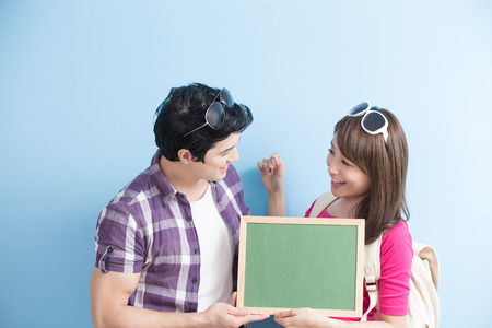 free education: young couple show blank green chalkboard to you with blue background