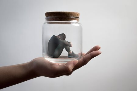 proble: the depression man sit imprisoned in jar Stock Photo