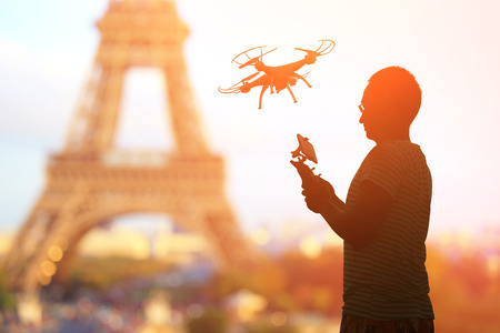 silhouette of man play drone in the sunset with Paris eiffel