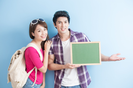 university students: young couple show blank green chalkboard to you with blue background
