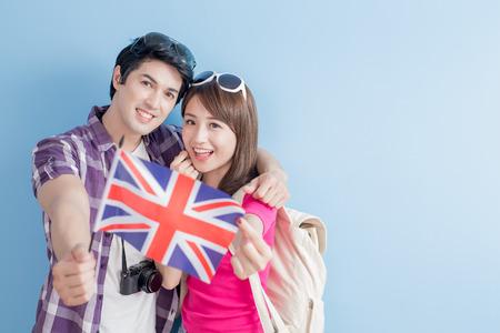 bandera japon: joven pareja lleve bandera británica y sonrisa feliz