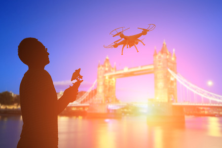 silhouette of man play drone in the sunset with tower bridge Stock Photo