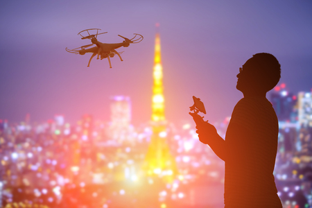 man flying: silhouette of man play drone in the sunset with tokyo tower