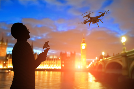 silhouette of man play drone in the sunset with big ben