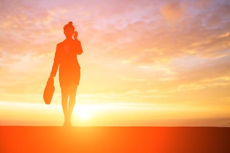 silhouette of businesswoman speak phone with sunset Stock Photo
