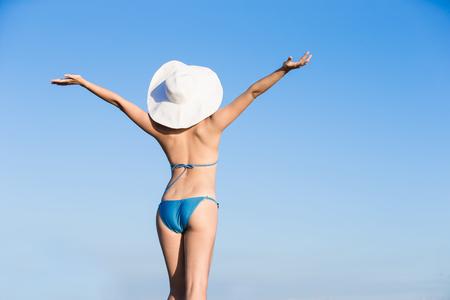 Schönheit Frau trägt Bikini zu Ihnen zurück und fühlen sich frei, mit blauem Himmel Standard-Bild - 75252857
