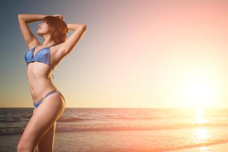 cintura: la belleza del desgaste de mujer bikini con la puesta del sol y el mar