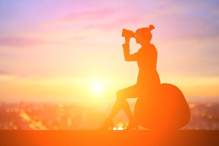 silhouette of business woman take binocular telescope with sunset