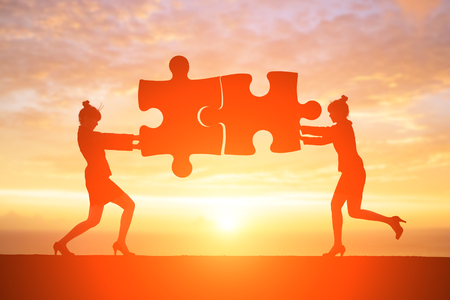 silhouette of businesswoman push puzzle with sunset Stock Photo