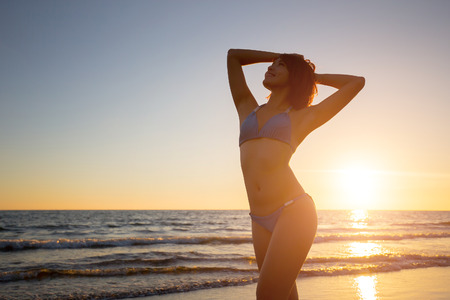 silhouette of beauty woman wear bikini with sunset