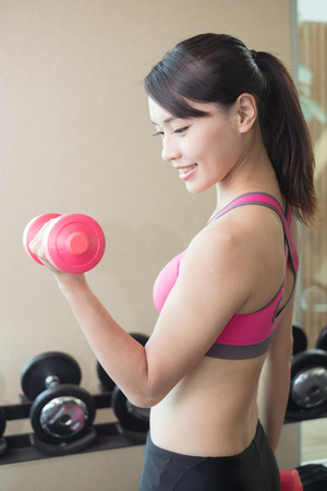 hard: sport woman hold dumbbell and training hard in the gym