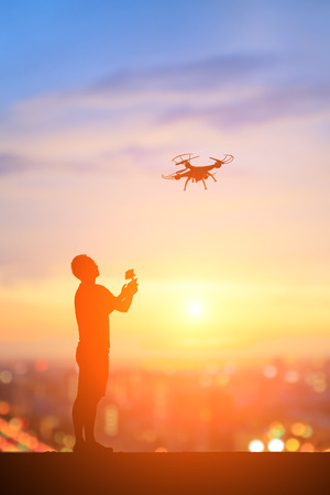 silhouette of man play drone with sunset
