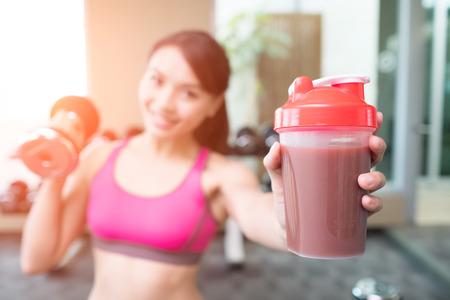 sport woman hold dumbbell and protein in the gym