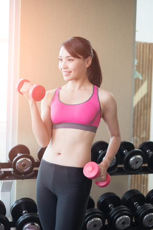 strong: sport woman hold dumbbell and training hard in the gym