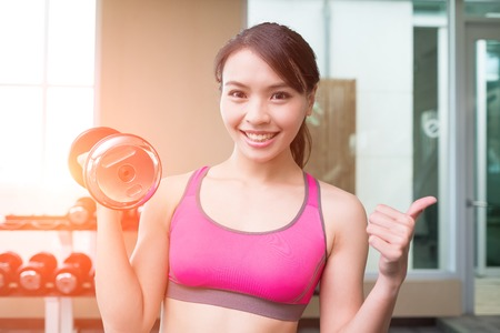 sport woman hold dumbbell and thumb up in the gym