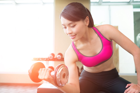 sport woman hold dumbbell and training hard in the gym