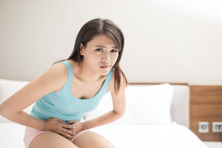 beauty woamn feel pain with menstruation on the bed Stock Photo