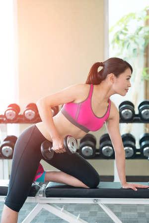muscle training: Sport Frau halten Hantel und hart trainieren in der Turnhalle