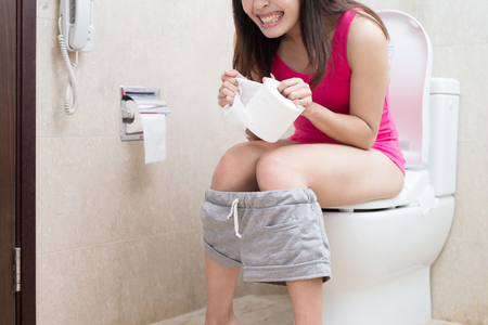 Frau fühlt Schmerzen mit Verstopfung im Badezimmer