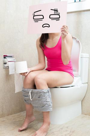 pantalones abajo: La mujer toma la cartelera confundir con el estreñimiento en el baño Foto de archivo