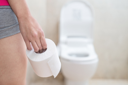woman take toilet paper in the bathroom