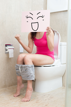 woman take smile billboard and feel excited in the bathroom Stock Photo