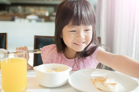 cute girl eat breakfast and smile happily