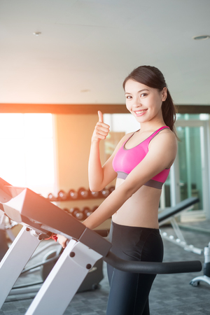 thumbup: woman smile happily and stand on treadmill in the gym Stock Photo