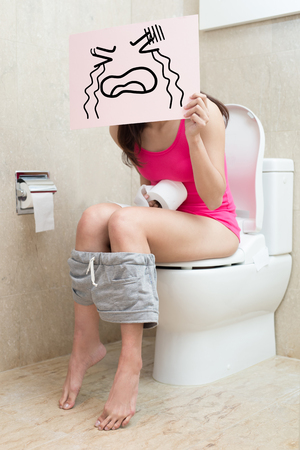 woman take cry billboard with constipation in the bathroom